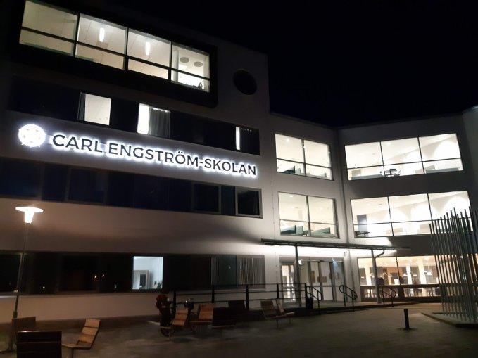 Foto på Carl Engström-skolan upplyst nattetid.