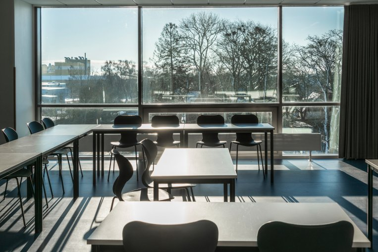 Foto från ett klassrum med bord och stolar.