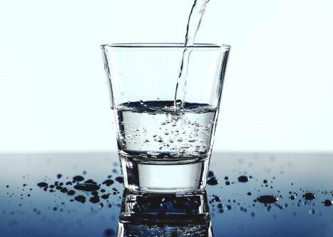 Halvfullt glas med vatten som fylls på.