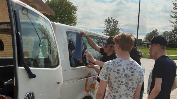 Ungdomar sätter solfilm på en ungdomsverksamhetens bil.