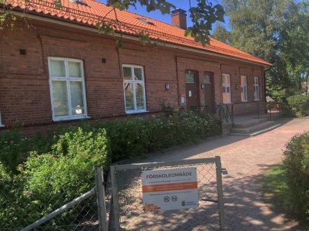 Förskola i ett plan byggt i rött tegel och med rött tegeltak. Buskar framför, grusgång oc halvöppen grind med skylt.