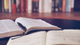 Två böcker som ligger uppslagna på ett bord. I bakgrunden står en bokhylla.