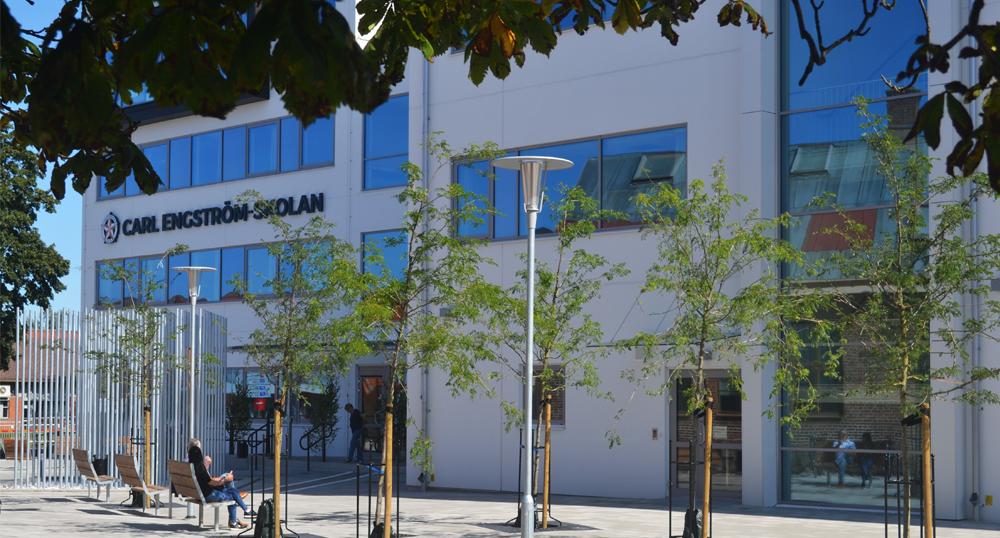 Bilden visar Carl Engström-skolans fasad och torget utanför byggnaden. Loggan syns på byggnaden.