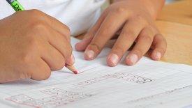 Bild på ett barn som räknar matte där endast händerna syns.