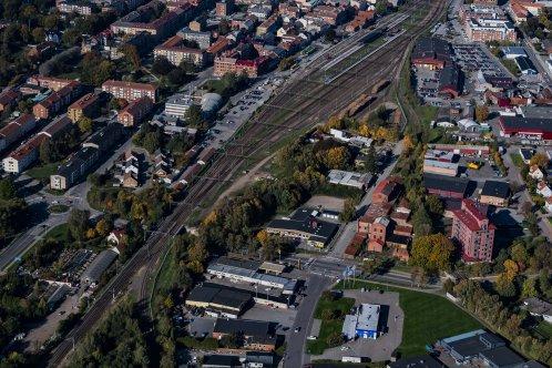 Flygbild över bangården med spår med stationen och alla spåren. Bebyggelse på båda sidor om spårområdet.