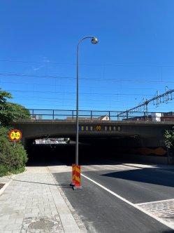 Lyktstople står mitt i cykelbana. Järnvägsbro i bakgrunden.