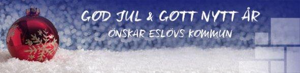 Julhälsing från Eslövs kommun med en röd julgranskula på snö mot bå bakgrund