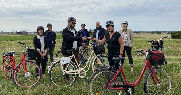 Sex personer står vid sina cyklar med Karaby backar i bakgrunden