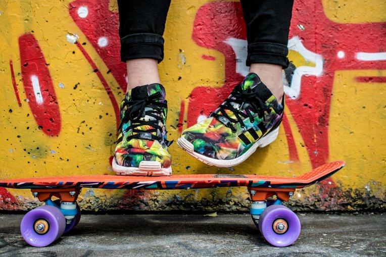 Färgglada skor och skateboard mot graffitivägg