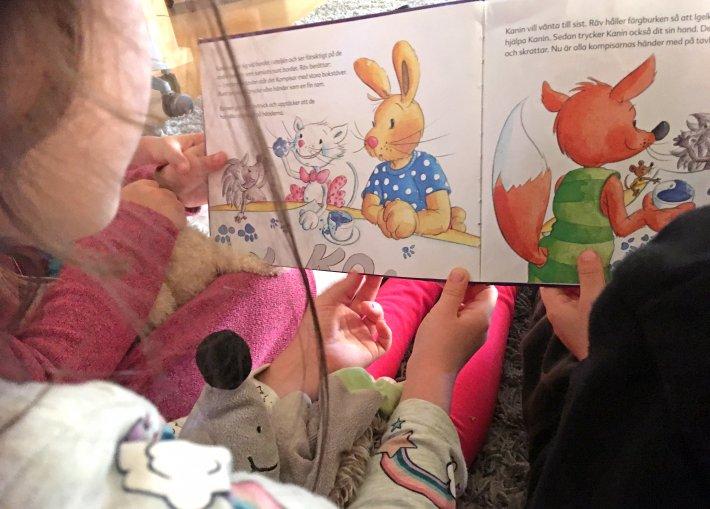 Barn tittar i en bok tillsammans med pedagog.
