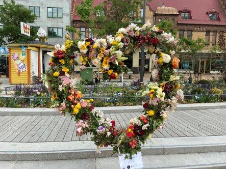 Hjärta av olika blommor med glasskiosken och hus på Södergatan i bakgrunden