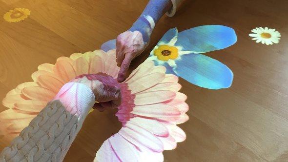 Händer som rör sig över en Tovertafel med blommor.