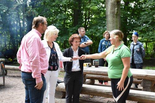 Stafettpinne i form av cykelpump lämnas över från Höörs representant till kommundirektör Eva Hellberg. Johan Andersson och Catharina Malmborg ser på. I bakgrunden tre personer från Eslövs scoutkår.