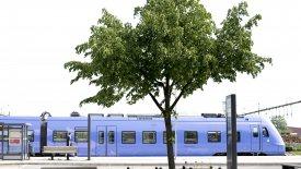 Bild på tåg på Eslövs station med träd framför