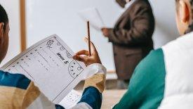 Två elever i förgrunden, den ena håller i ett papper. I bakgrunden syns en kvinnlig lärare som skriver på en whiteboard.