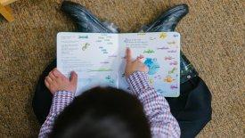 En pojke sitter med en bok i knät och pekar på texten.