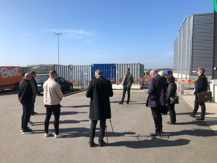 Personer som står i en ring runt David Mårtensson. Byggnad och containrar i bakgrunden.