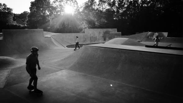 Svartvitt fotografi. Tre personer åker skateboard i en skatepark. Träd i bakgrunden och solen strålar igenom.