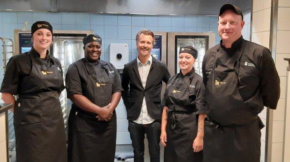 Fem personer på rad med skolans kök i bakgrunden