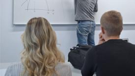 Två elever lyssnar på en pedagog som skriver på en white board.